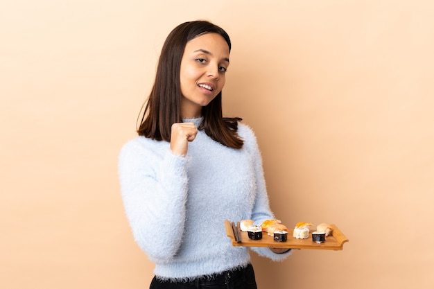 Young brunette mixed race woman holding sushi proud and self-satisfied