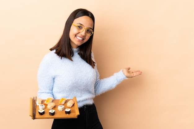 Young brunette mixed race woman holding sushi over wall extending hands to the side for inviting to come