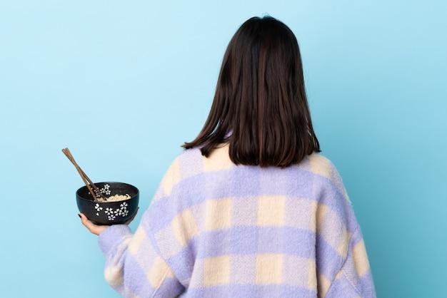 Молодая брюнетка смешанной расы женщина над изолированной синей стеной в заднем положении, держа миску лапши с палочками для еды.