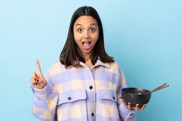 Молодая женщина смешанной расы брюнет над изолированной голубой стеной указывая вверх отличную идею, держа миску лапши с палочками для еды.