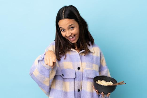 孤立した青い壁の上の若いブルネット混血の女性は、箸で麺のボウルを保持しながら自信を持ってあなたに指を指しています。