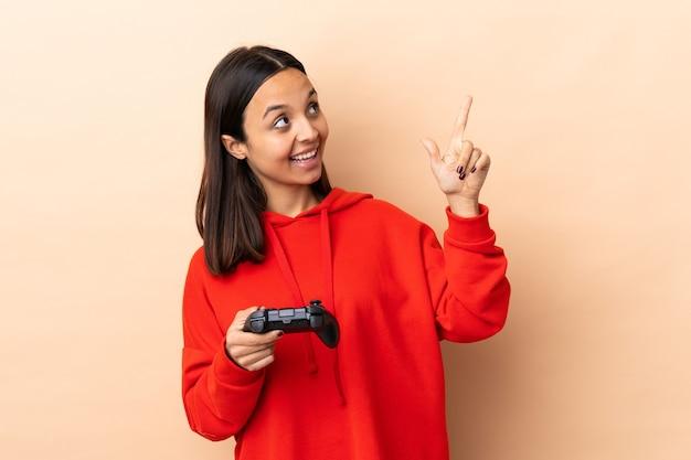 人差し指で指している孤立した背景の上にビデオゲームコントローラーで遊ぶ若いブルネット混血の女性素晴らしいアイデア