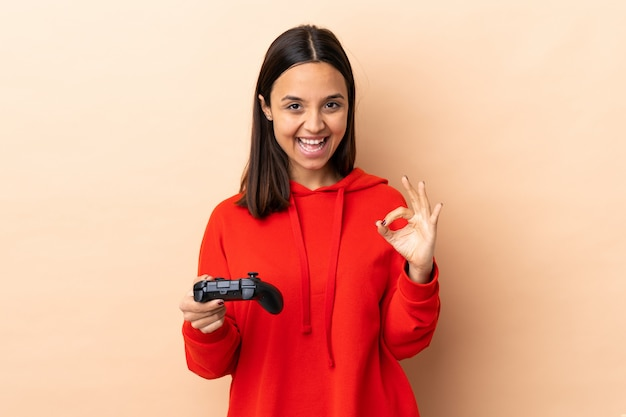 Young brunette mixed race woman playing with a video game controller over isolated background showing an ok sign with fingers
