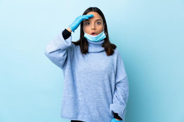孤立した青い壁の上のマスクと手袋でコロナウイルスから保護する若いブルネットの混血女性が何かを実現し、解決策を意図