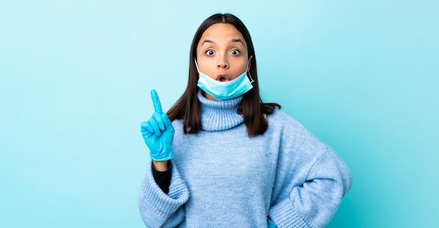 指を持ち上げながら解決策を実現しようとしている青い壁の上のマスクと手袋で保護する若いブルネットの混血の女性