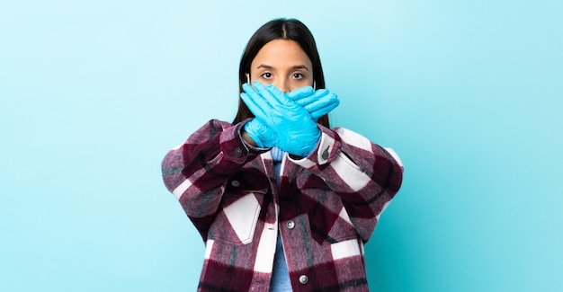 Young brunette mixed race woman protecting with a mask and gloves over blue wall making stop gesture with her hand