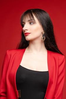 風船に近いポーズ赤い衣装の若いブルネットモデル