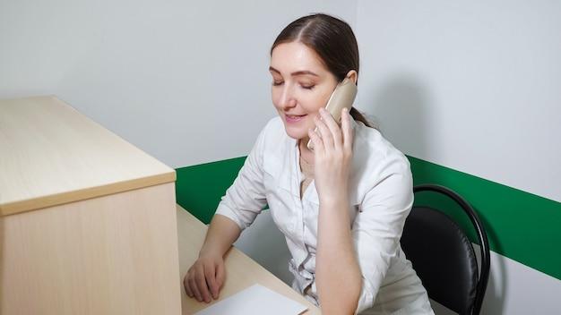 흰 코트를 입은 젊은 브루네트 간호사가 진료소 리셉션 데스크에서 일하고 있으며, 그녀는 전화를 받고 약속을 잡고 있다