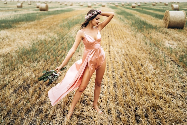 Young brunette in a pink satin dress in a wheat field near hay bales. a woman has a wreath on her head and holds a bouquet of wildflowers in her hands