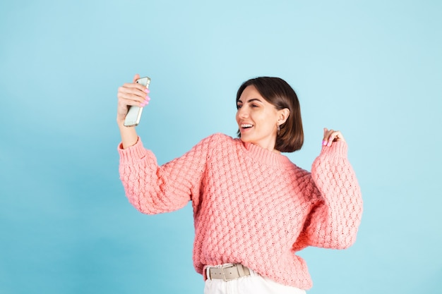 Young brunette in pink sweater isolated on blue wall