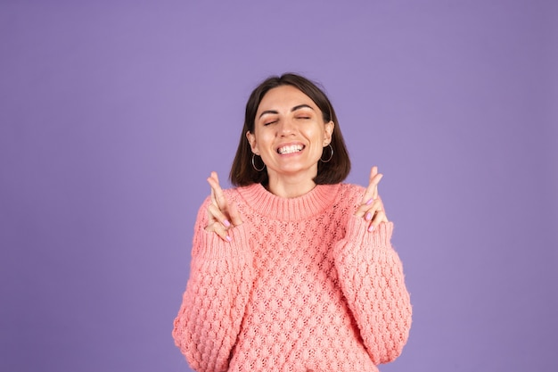 Young brunette in pink sweater isolated on purple wall
