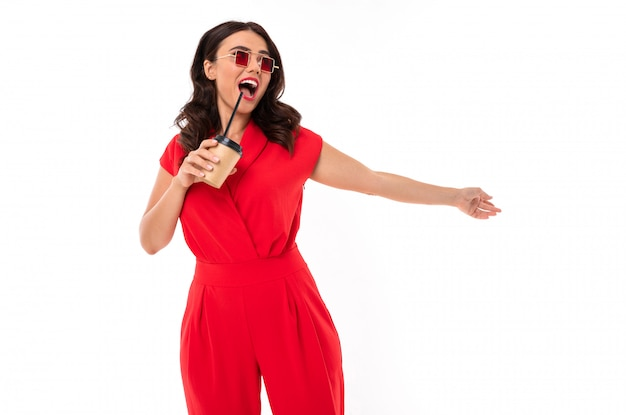 Young brunette in a red dress with a glass of coffee in her hands, a girl in sunglasses with a smile