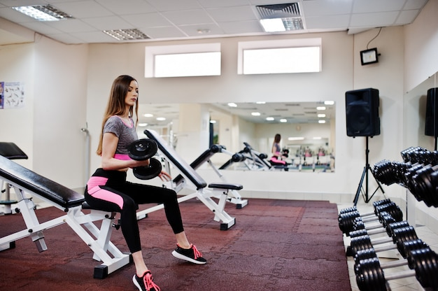 Young brunette sexy slim woman doing workout at gym.