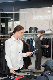 Young brunette shop assistant using touchpad while elegant man looking through new collection of jackets on background