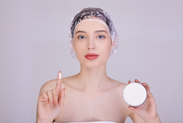 A young brunette in a shower cap is holding a cream.