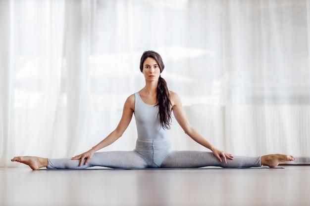 Молодая брюнетка сидит на коврике с раздвинутыми ногами. концепция здорового образа жизни.