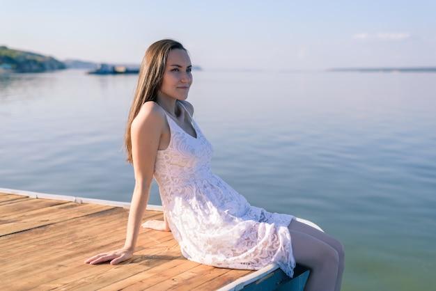 일몰에 흰색 sundress에 부두에 앉아 젊은 갈색 머리