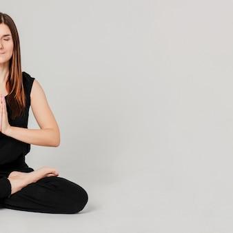 分離されたヨガの蓮華座に座っている黒の若いブルネットスリムな女性