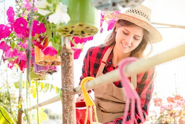 若いブルネットの笑顔の女性は親切に温室で花を扱います。カラフルで活気のある画像