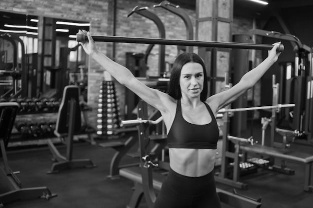체육관에서 그녀의 손에 바디 바 체조 운동을 하 고 젊은 갈색 머리 sportwoman