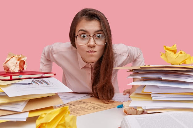 Молодая брюнетка студент сидит за столом с книгами