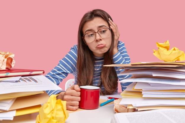 本と机に座っている若いブルネットの学生