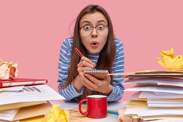 책을 책상에 앉아 젊은 갈색 머리 학생