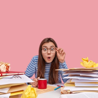 Young brunette student sitting at desk with books