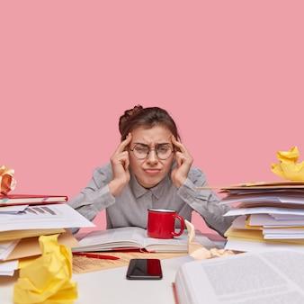 Giovane studentessa bruna seduto alla scrivania con i libri