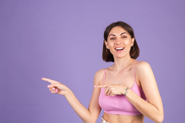 Young brunette in top isolated on purple wall