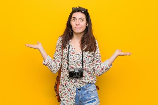 若いブルネットの旅行者の女性は、コピースペースを保持するために混乱し、疑わしい肩をすくめる。