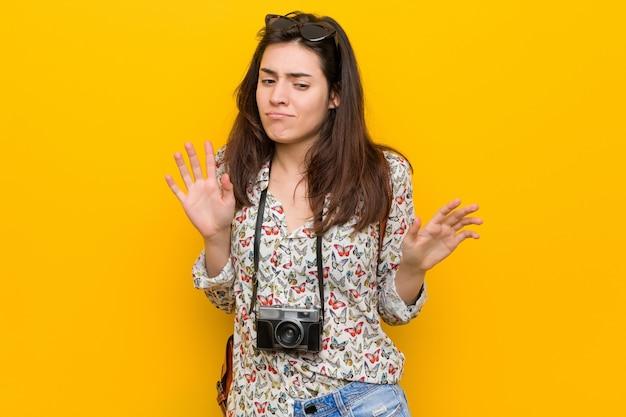 혐오의 제스처를 보여주는 사람을 거부하는 젊은 갈색 머리 여행자 여자.