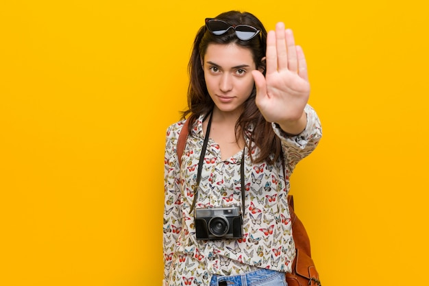 Young brunette traveler woman standing with outstretched hand showing stop sign, preventing you.