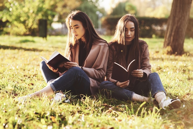 Young brunette twin sisters sitting close to each other on the grass with legs slightly bent in knees and crossed, reading brown books, wearing casual coat in autumn sunny park on blurry background.