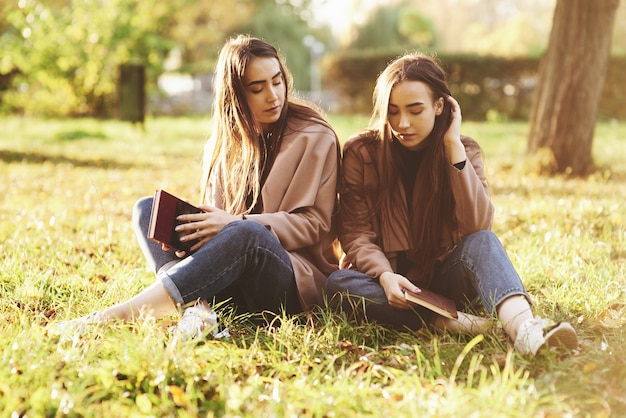 Young brunette twin sisters sitting close to each other with eyes closed on the grass,legs slightly bent in knees and crossed, holding brown books,wearing casual coat in autumn park on background.