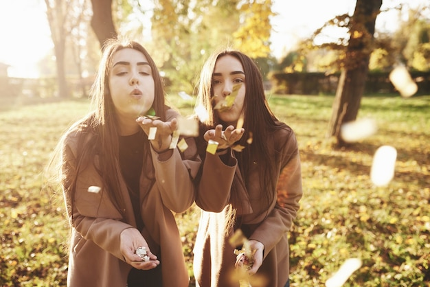 Young brunette twin sisters standing close to each other and blowing confetti into camera, holding some of those in their hands, wearing casual coat in autumn sunny park on blurry background.