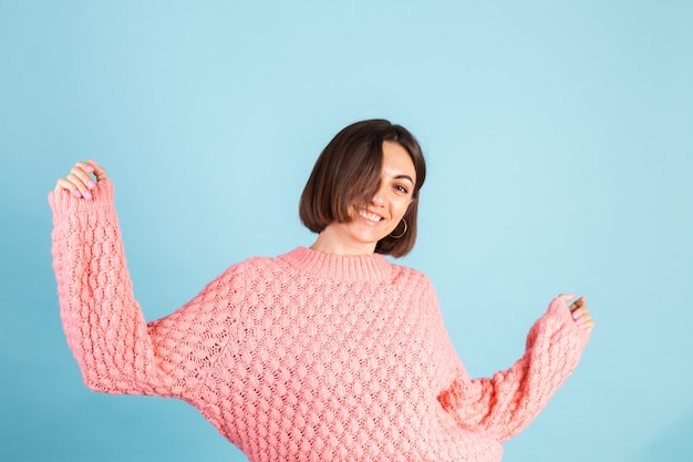 Young brunette in warm pink sweater isolated on blue wall