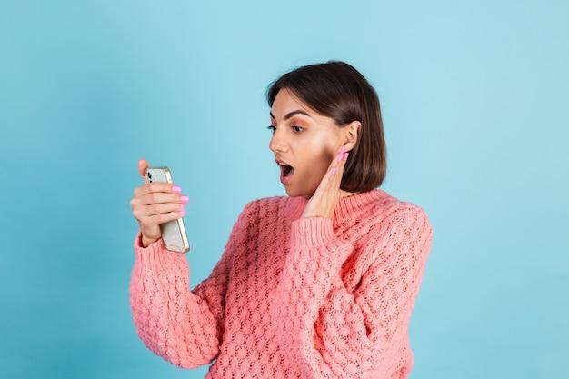 Giovane bruna in caldo maglione rosa isolato sulla parete blu