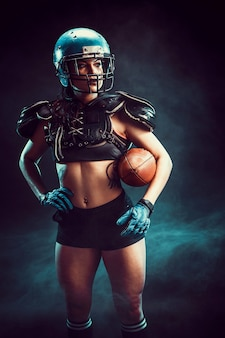 Young brunette wearing sexy uniform of rugby football player posing with ball.