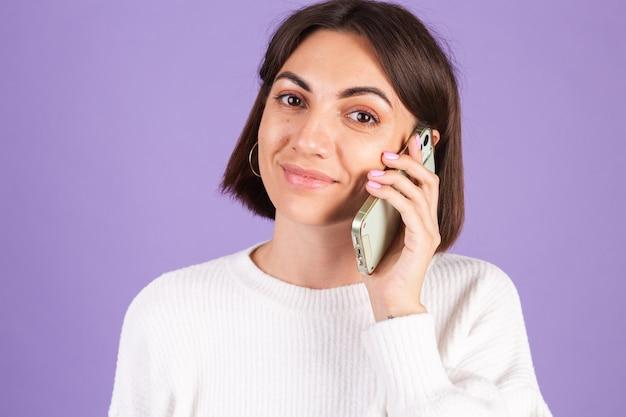 Giovane bruna in maglione casual bianco isolato sulla parete viola