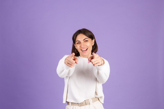Young brunette in white casual sweater isolated on purple wall