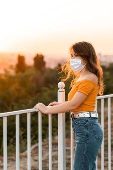 Молодая брюнетка с хирургической маской на лице держится за забор и смотрит на закат в общественном парке.