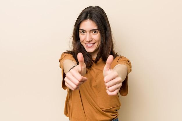 親指を立てて、何かについて歓声を上げ、コンセプトをサポートし、尊重するベージュの空間に対して若いブルネットの女性。