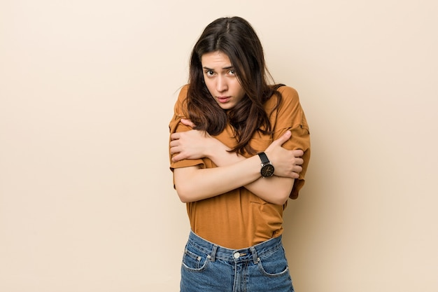 Young brunette woman against a beige background going cold due to low temperature or a sickness.