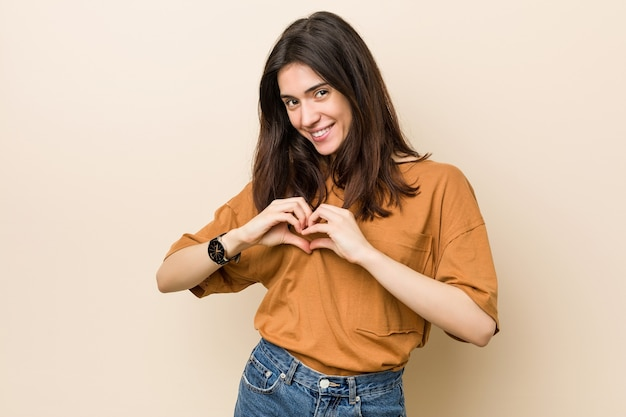 Young brunette woman against a beige background smiling and showing a heart shape with hands.