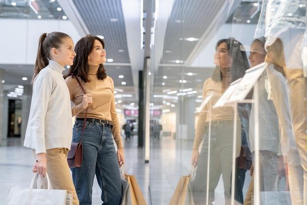 若いブルネットの女性と彼女の娘のカジュアルな服装で店の窓際に立って、新しい季節のコレクションを見て