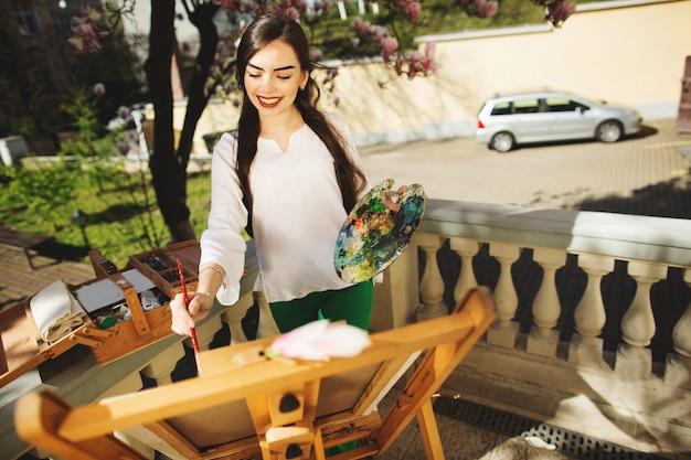 Молодая брюнетка женщина художник держит в руках кисти и палитры.