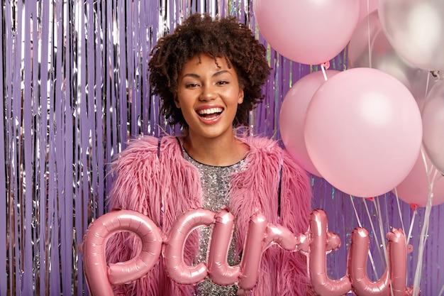風船を保持しているパーティーで若いブルネットの女性