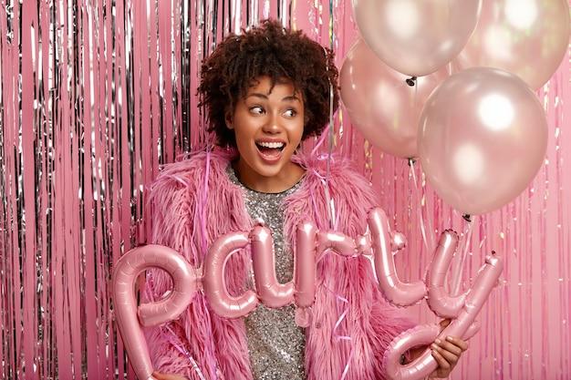 Молодая брюнетка женщина на вечеринке, держа воздушные шары