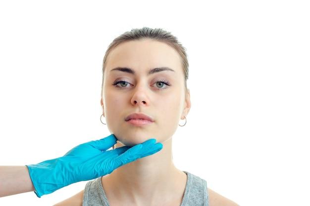 Молодая брюнетка женщина у пластического хирурга изолирована на белой стене